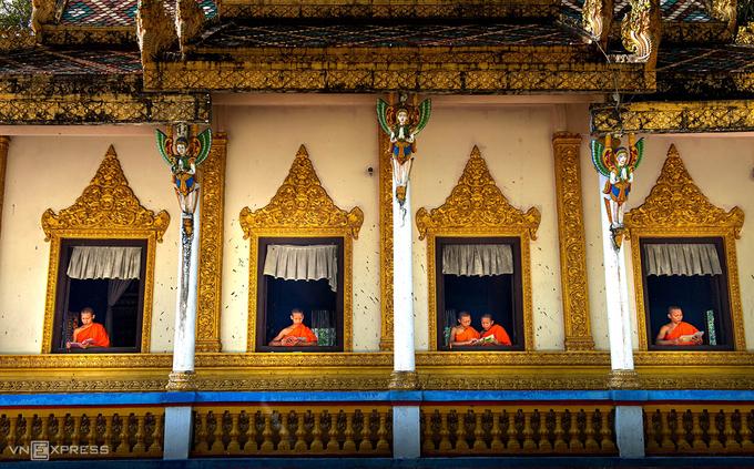 Những vị sư đọc sách bên khung cửa. Phía trên các cột là tượng đắp nổi mô tả cảnh tiên nữ Khmer chắp tay hành lễ.