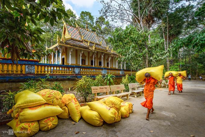 Các nhà sư của chùa khiêng những bao lúa vừa thu hoạch xong vụ đông xuân. Hình ảnh nhà sư lao động thu hoạch lúa hay phụ xây chùa là một nét đặc trưng tại các ngôi chùa Khmer Nam Bộ.