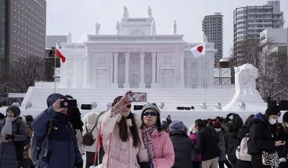 Du khách chụp hình với các tác phẩm nghệ thuật bằng băng và tuyết tại Lễ hội tuyết Sapporo hằng năm tại Hokkaido - Ảnh: EPA