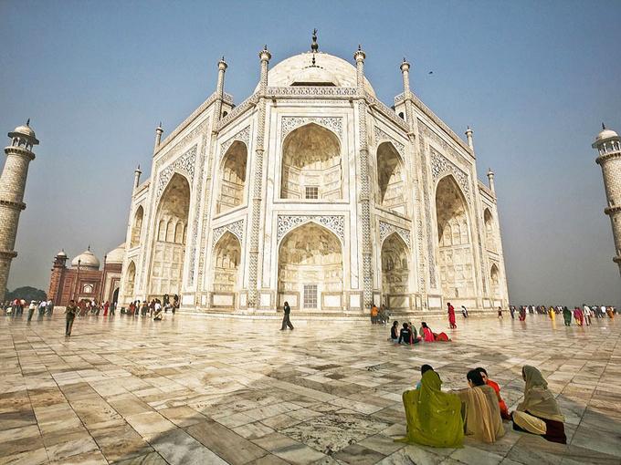 Khu lăng mộ chính được xây cao với phần sân xung quanh rộng rãi, từ đây có thể dễ dàng nhìn ngắm toàn cảnh xung quanh. Công trình chủ yếu xây bằng đá cẩm thạch trắng - gam màu chủ đạo của các kiến trúc Hồi giáo.  Một trong những nét độc đáo của Taj Mahal chính là lối kiến trúc đối xứng trên nền móng hình vuông với 4 cửa vòm, ban công, cửa sổ, tháp... Để xây dựng, nhiều thợ xây, cắt đá, khảm, hoạ sĩ, thư pháp từ khắp Trung Á, Iran... được huy động về đây. Khoảng 20.000 người đã làm việc ngày đêm trong khoảng 20 năm để hoàn tất lăng mộ. Ảnh: Taj Mahal.