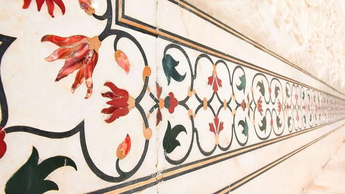 Khảm đá quý là một nét ấn tượng khác trong nghệ thuật kiến trúc của Taj Mahal. Theo hướng dẫn viên địa phương, đá cẩm thạch sau khi được vận chuyển từ vùng Rajasthan về, được thợ vẽ và đục theo các đường nét. Đá quý nhiều màu cũng được mài sao cho vừa với phần rỗng đã đục sẵn trên đá cẩm thạch và khảm đến nhẵn mịn như cùng một khối. Buổi tối, các họa tiết này nếu có ánh sáng (mặt trăng) chiếu vào sẽ rực sáng lấp lánh. Ảnh: Wiki.