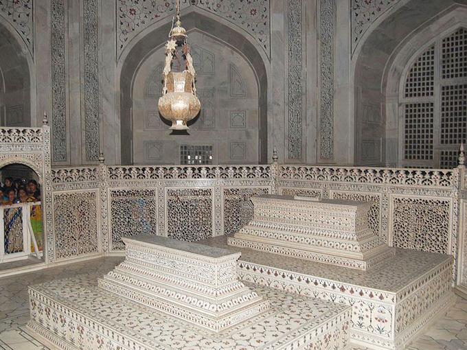 Bên trong lăng là khu vực du khách không được phép chụp hình. Nơi này đặt mộ của vua Shah Jahan (phải) và hoàng hậu Mumtaz Mahal. Do lăng mộ được vua xây tặng sau khi hoàng hậu qua đời, nên mộ của Mumtaz Mahal đặt ở chính giữa. Shah Jahan sau khi mất mới được con trai đặt an nghỉ cạnh người vợ ông yêu quý nhất. Đây được cho chi tiết bất đối xứng duy nhất trong lăng.  Tuy nhiên, hai phần mộ được quây rào cho phép du khách tham quan thực chất là bản mô phỏng của hầm mộ thật phía dưới. Nhờ những lỗ nhỏ được đục rỗng bằng ngón tay trên các bức tường đá mà bên trong lăng vẫn thông thoáng, không quá tối. Ảnh: Taj Mahal.