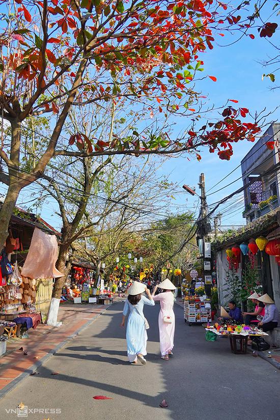 Hai phụ nữ trong tà áo dài khám phá nhịp sống Hội An trên đường Nguyễn Thị Minh Khai. Hội An có những con đường ngắn và hẹp, chạy dọc và ngang theo hình bàn cờ, cứ đi hết hẻm này là gặp hẻm khác.