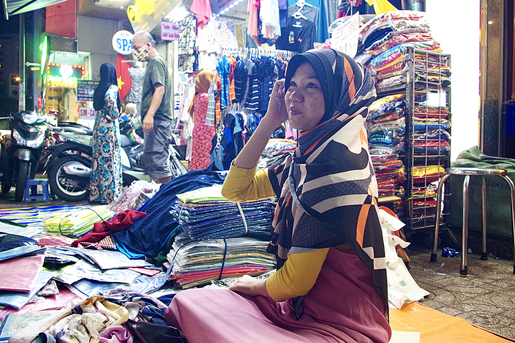 Các cô gái bán hàng sẵn sàng làm người mẫu thử khăn cho khách. Ảnh: Tâm Linh.