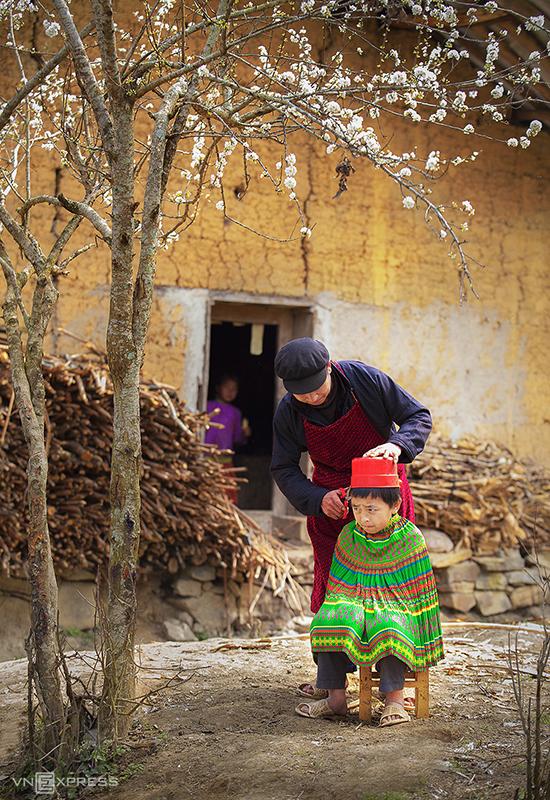 Người cha cắt tóc cho con bên hiên nhà tại xã Lũng Cú, Đồng Văn.  Du khách đến Hà Giang thường ghé check-in cột cờ nằm ở đỉnh Lũng Cú hay còn gọi là đỉnh núi Rồng cao khoảng 1.470 m so với mực nước biển, thuộc xã cực Bắc của Tổ quốc.