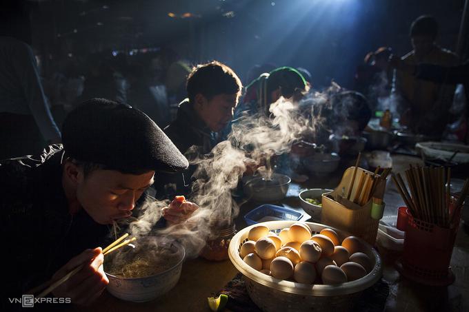 """Trải nghiệm mùa xuân nơi cao nguyên đá, du khách đừng quên thưởng thức bữa sáng tại chợ phiên Đồng Văn.  Bức ảnh """"Bữa sáng ở chợ phiên"""" đạt giải thưởng Grand Prize tại cuộc thi ảnh quốc tế do tạp chí Smithsonian (Mỹ) tổ chức năm 2018. Một năm sau, bức ảnh tiếp tục đạt huy chương bạc Liên hoan Ảnh nghệ thuật quốc tế lần thứ 10 tại Việt Nam."""