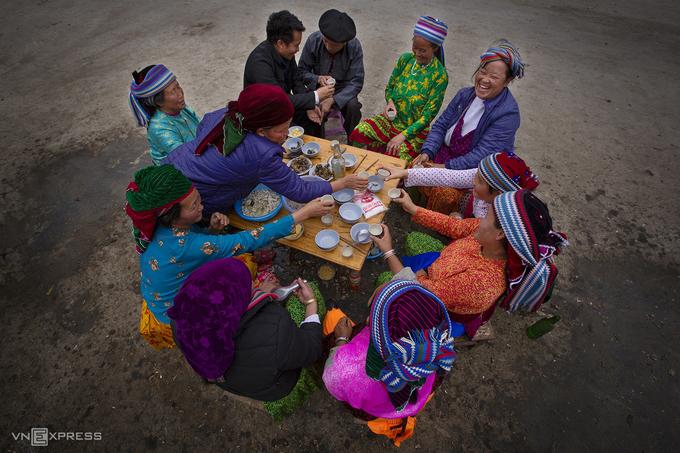Trong tiết trời xuân Phố Cáo, một nhóm người dân tươi cười lúc thưởng thức rượu và các món ăn vùng cao.