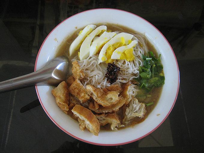 Bún gồm một quả trứng luộc thái lát và akyaw (rau chiên giòn) cùng một đĩa bột đậu lăng. Ảnh: Saveur.