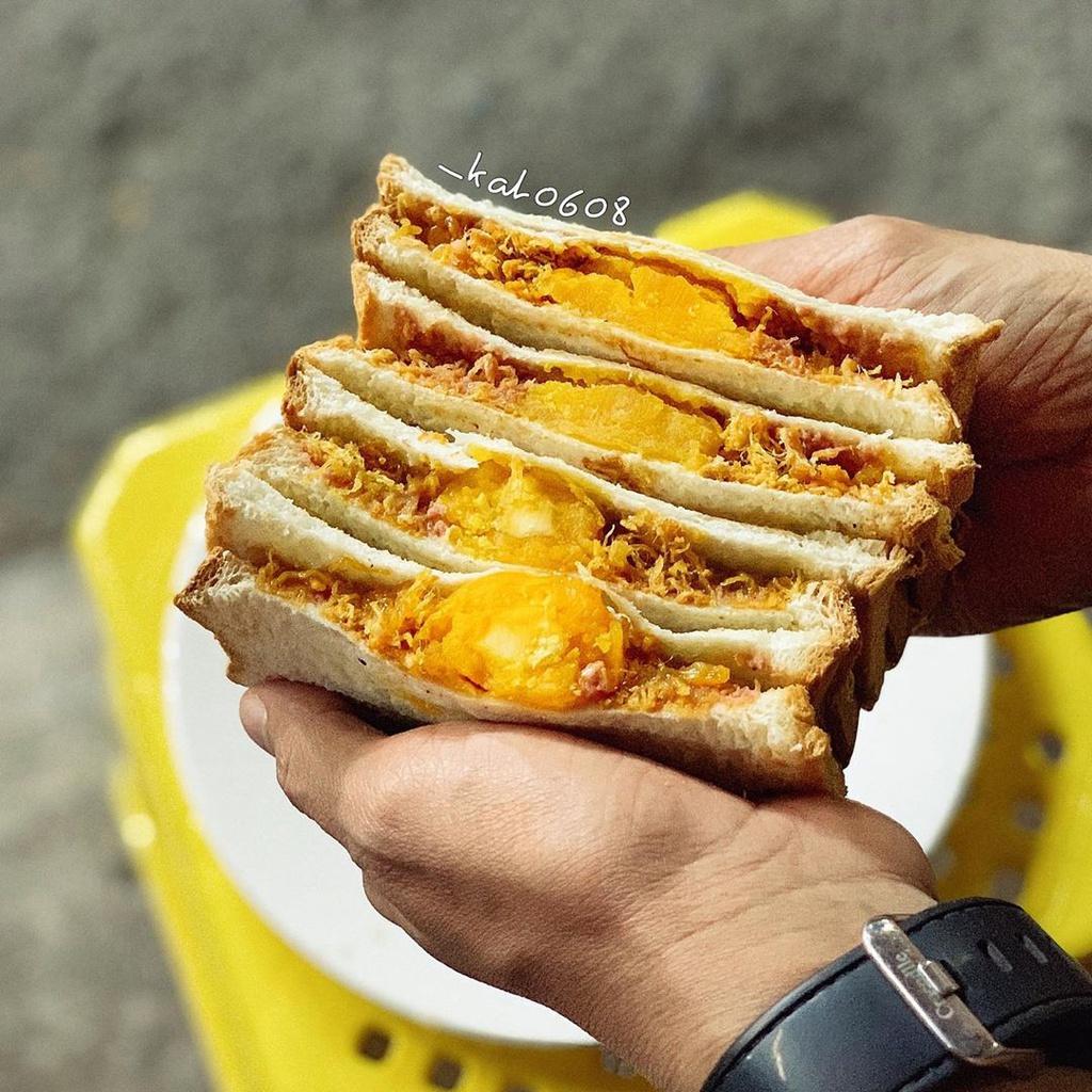 Sandwich trứng muối chà bông pate là món ăn vặt đang hot ở TP.HCM thời gian gần đây. Bánh được nướng giòn rụm, thêm bơ, pate, chà bông, trứng muối bên trong. Thưởng thức món bánh này bạn sẽ cảm nhận được vị giòn, mặn, ngọt hấp dẫn. Giá: 20.000-35.000 đồng. Địa chỉ: 71/25B Cô Bắc, quận 1. Ảnh: _kat0608.