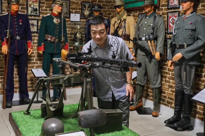 """Anh Tân (ảnh - một du khách) chăm chú nhìn khẩu súng máy MG4, do Đức sản xuất, sử dụng trong những năm 1930. """"Bảo tàng trưng bày rất phong phú, chú thích rõ ràng về các loại vũ khí, quân phục trên thế giới. Tôi thích nhất những bộ áo giáp mà lính của các triều đại phong kiến Trung Quốc mặc, trong khi trước giờ chỉ nhìn thấy trong phim ảnh"""", du khách đến từ Long An nói.  Bảo tàng vũ khí cổ mở cửa các ngày trong tuần với giá vé người lớn 70.000 đồng và 35.000 đồng cho trẻ em dưới 12 tuổi."""