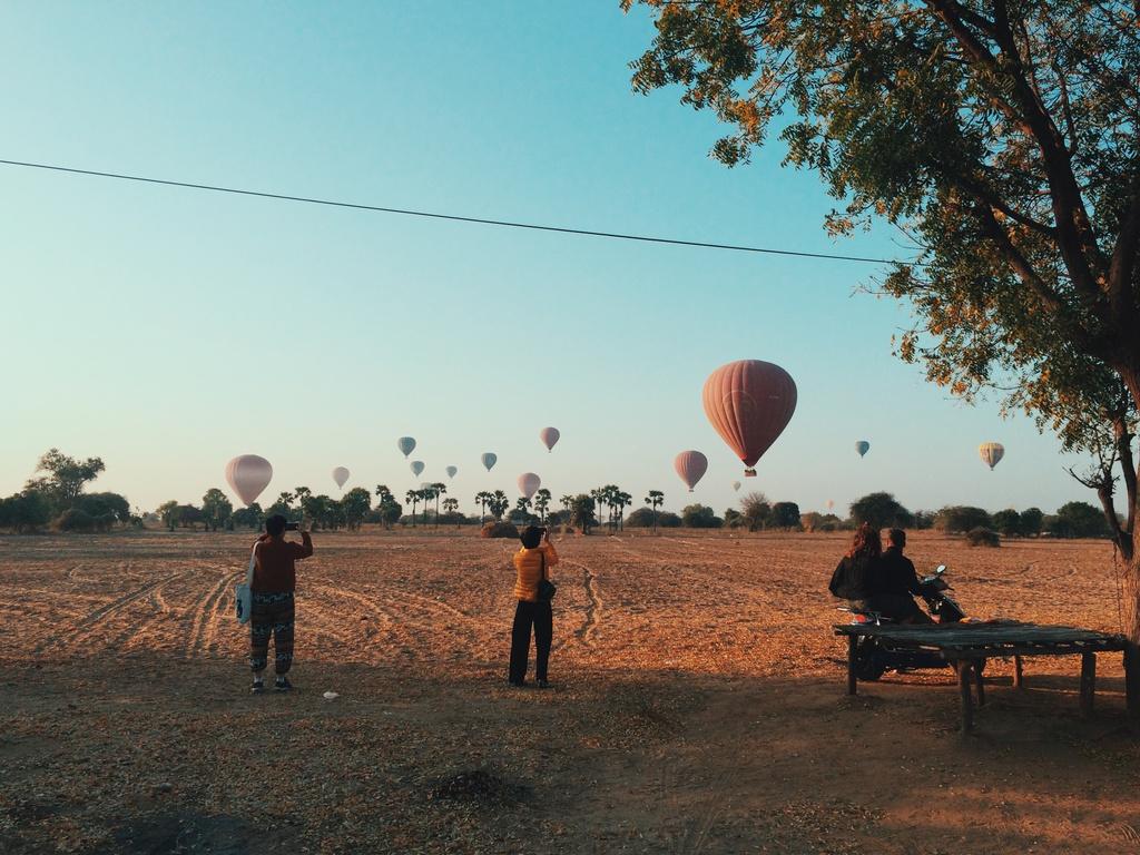 Tôi tìm được 2 điểm ngắm bình minh tuyệt đẹp. Một là bạn nên thuê xe và nhờ tài xế chở đến Balloon Station ở Nyaung-U để trải nghiệm khoảnh khắc vào lúc bình minh, những quả khí cầu khổng lồ bơm căng phồng trong ánh lửa bay lên ngay trước mắt. Hai là trên đường từ trạm xe buýt ở Nyaung-U trở về New Bagan, bạn sẽ gặp một cánh đồng cỏ khô với những khoảng trống lớn, đủ để ngắm được những quả khí cầu vào khoảnh khắc chúng đồng loạt hạ xuống ở New Bagan.