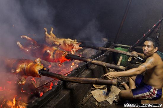 """Các đầu bếp """"bậc thầy"""" phải đảm bảo thịt lợn được chín đều bằng cách xoay liên tục, thi thoảng sẽ rưới nước dừa và hỗn hợp gia vị lên thịt. Ảnh: CNN/Derrick Chang."""