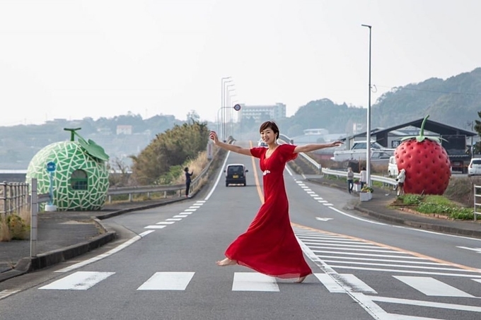"""Nhà chờ hình dâu tây, dưa lưới, cà chua, cam, dưa hấu sơn màu bắt mắt, bên trên có cuống lá màu xanh. Nhiều người gọi đây là """"insta-bae"""" bởi nó khá nổi tiếng trên instagram, khiến không ít người lầm rằng nhà chờ hoa quả được xây dựng nhằm mục đích quảng bá. Thực chất, đây là mô hình sử dụng trong một hội chợ du lịch tổ chức tại Nagasaki vào năm 1990, sau đó mới chuyển về thị trấn Konagai làm trạm xe buýt. Ảnh sato.min13"""