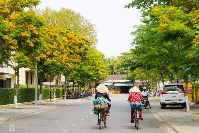Hai phụ nữ đạp xe bán hàng trên đường Phan Chu Trinh. Covid-19 khiến Hội An vắng khách tham quan, đường phố vì thế tĩnh lặng hơn.