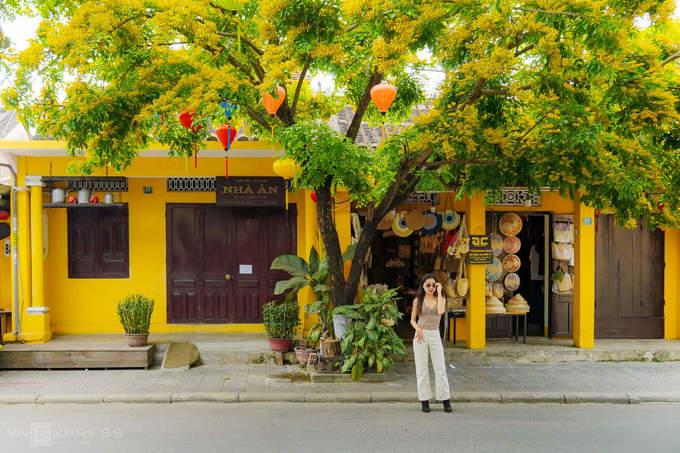 Nữ du khách chụp hình trước một cửa hàng bán nón lá trên đường Phan Chu Trinh.