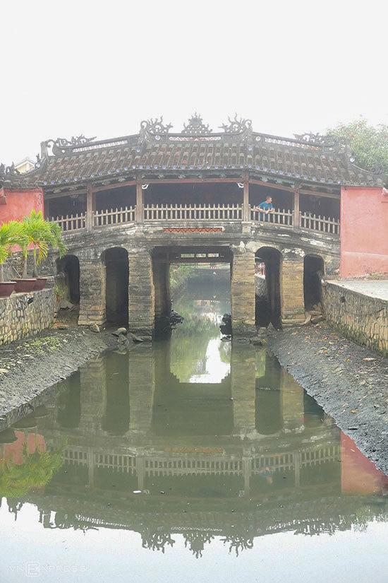 Chùa Cầu mờ ảo trong màn sương sớm. Ngôi chùa nằm vắt ngang con lạch nhỏ chảy ra sông Hoài, một nhánh của dòng sông Thu Bồn là hình ảnh biểu tượng của phố cổ Hội An, đồng thời được in trên tờ tiền 20.000 đồng đang lưu hành.