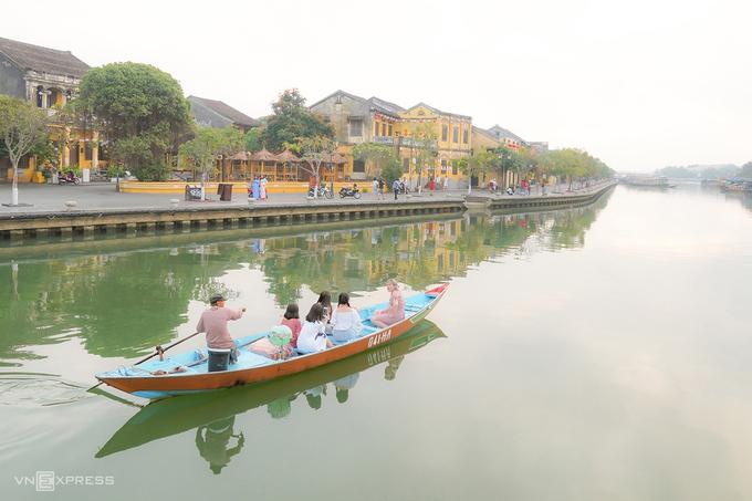 """Con thuyền chở du khách tham quan trên sông Hoài dưới ánh nắng đầu ngày, khi bầu không khí còn hơi sương. """"Ngồi trên con thuyền nhỏ lướt êm đềm qua những dãy phố, làng nghề hai bên bờ sông sẽ là một trải nghiệm thú vị với du khách"""", nhiếp ảnh gia Đỗ Anh Vũ (sống tại Hội An), tác giả bộ ảnh, cho biết."""