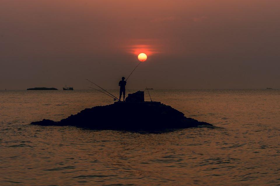 Thời điểm thủy triều bắt đầu dâng cao báo hiệu hoàng hôn sắp đến. Mặt trời lặn dần xuống biển, tạo thành cảnh tượng huyền ảo với sắc đỏ, hồng, tím xen lẫn trên nền trời. Mặt trời đỏ rực phát đi tất cả tia nắng cuối cùng của ngày rồi chìm dần xuống biển, có lúc ẩn sau đám mây, có lúc nằm một nửa trên mặt biển. Ảnh: Trần Tuấn Anh.