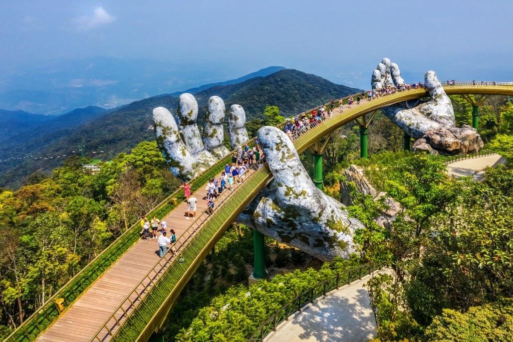 Cầu Vàng, Đà Nẵng  Nằm ở độ cao 1.414 m so với mực nước biển, Cầu Vàng (thuộc khu du lịch Bà Nà Hills) có thiết kế hình vòng cung, được nâng đỡ bởi 2 bàn tay khổng lồ, vươn ra nền trời xanh. Cây cầu dài 150 m và rộng 12,8 m với 8 nhịp là điểm trung chuyển từ làng Pháp tới vườn Thiên Thai ở khu du lịch. Được hoàn thiện và khánh thành năm 2018, cây cầu thu hút nhiều du khách trong và ngoài nước tới tham quan, chụp ảnh.