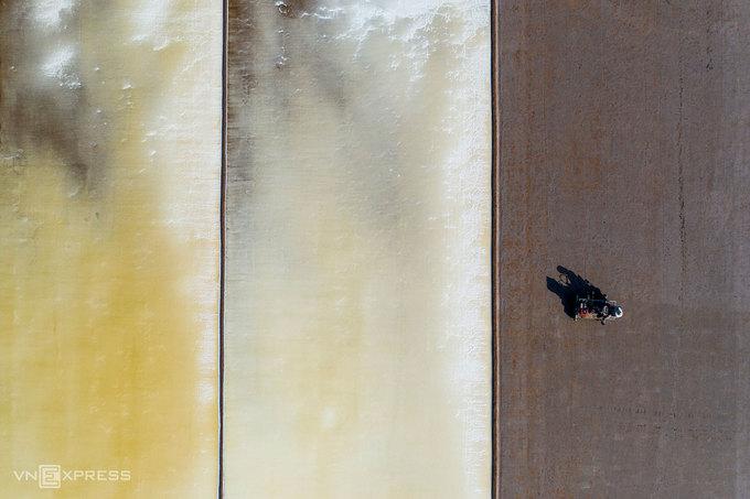 Những ruộng muối ở ven biển nhìn từ trên cao. Làm muối là nghề vất vả, thấm đượm mồ hôi. Trước khi vào sản xuất, diêm dân phải trữ nước và làm sân phơi thật kỹ, cải tạo bằng xe cơ giới, lu phẳng để mặt sân chắc chắn. Đây là công đoạn làm đất trước khi dẫn nước biển vào ruộng.