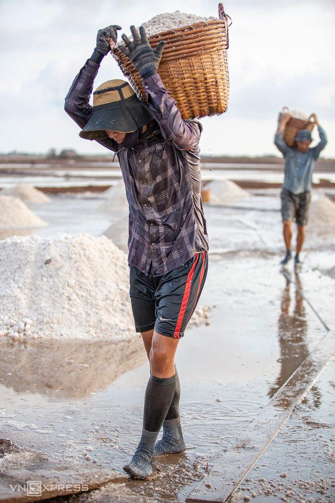 """Ngoài xe đẩy, cần xé là dụng cụ thiết yếu để đựng muối trong quá trình thu hoạch. Mỗi cần xé muối có trọng lượng 40kg, đôi khi cần xé trượt xuống làm trầy vai người vác, muối xát vào da nhưng các diêm dân vẫn bám nghề.  """"Người làm muối luôn cầu mong nắng gắt, trời thương cho nắng nhiều thì cào muối có lãi"""", anh Lĩnh, người vác cần xé muối phía sau ảnh chia sẻ."""