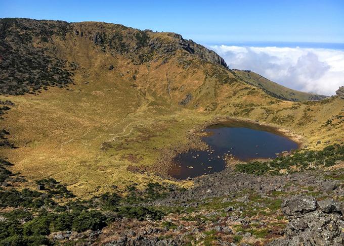 """Hallasan vốn là ngọn núi lửa được hình thành từ hàng triệu năm trước nhưng đã ngừng hoạt động. Bao quanh là thảm thực vật, cảnh quan núi đồi, tạo nên hòn đảo Jeju nổi tiếng. Đỉnh Hallasan chính là """"trái tim"""" của Jeju mà bất cứ du khách nào tới đây cũng muốn check in."""