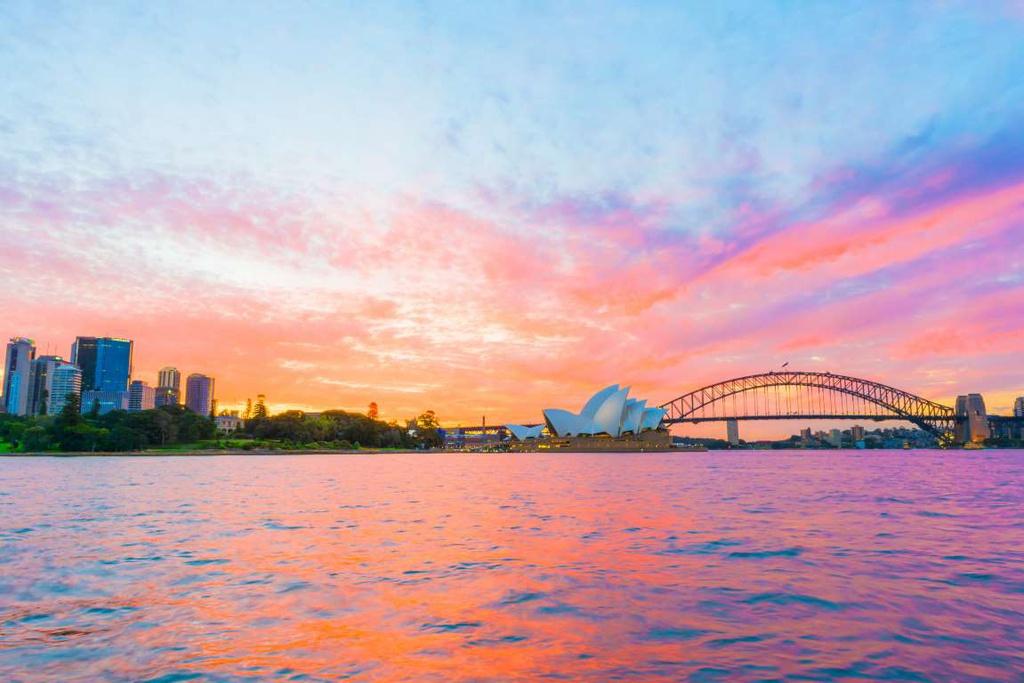 """Sydney (Australia): Opera Syney hay """"nhà hát con sò"""" trở nên nổi bật dưới ánh hoàng hôn. Các công trình kiến trúc hiện đại phản chiếu xuống mặt nước nhuốm màu cam, tím, tạo nên khoảnh khắc cuối ngày ấn tượng."""