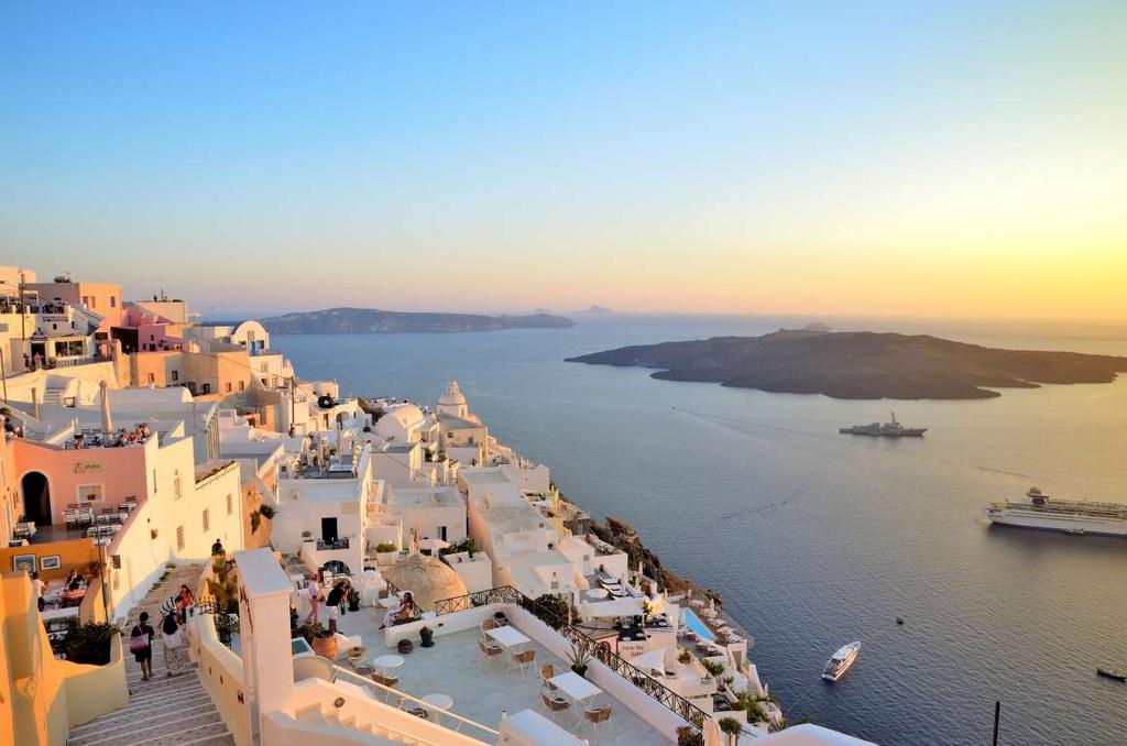 Santorini (Hy Lạp): Những ngôi nhà tone trắng, xanh trở nên ấm áp hơn dưới thời khắc hoàng hôn. Bờ biển Aegean được nhuộm màu rực rỡ, là điểm ngắm mặt trời lặn tuyệt đẹp ở Hy Lạp.