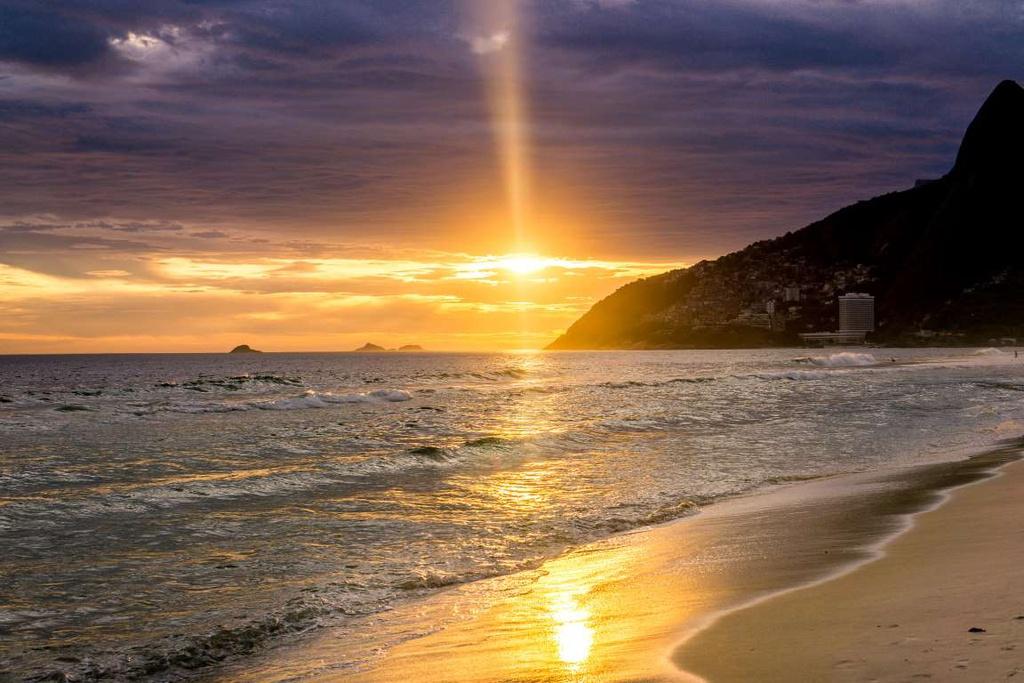 """Rio de Janeiro (Brazil) sở hữu những bãi biển xanh trong, quyến rũ, thiên nhiên tươi đẹp. Khung cảnh """"mặt trời xuống biển Ipanema"""" cũng rực rỡ không kém, thu hút các du khách đến với Brazil."""