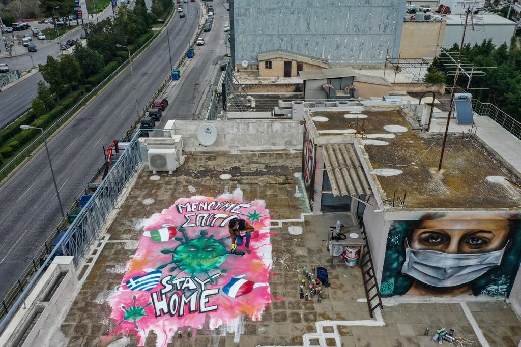 """Trên nóc chung cư tại Athens, Hy Lạp, một nghệ sĩ 16 tuổi đang thực hiện tác phẩm phun sơn rực rỡ, thông điệp """"Hãy ở nhà"""" để chống dịch Covid-19 được thể hiện nổi bật."""