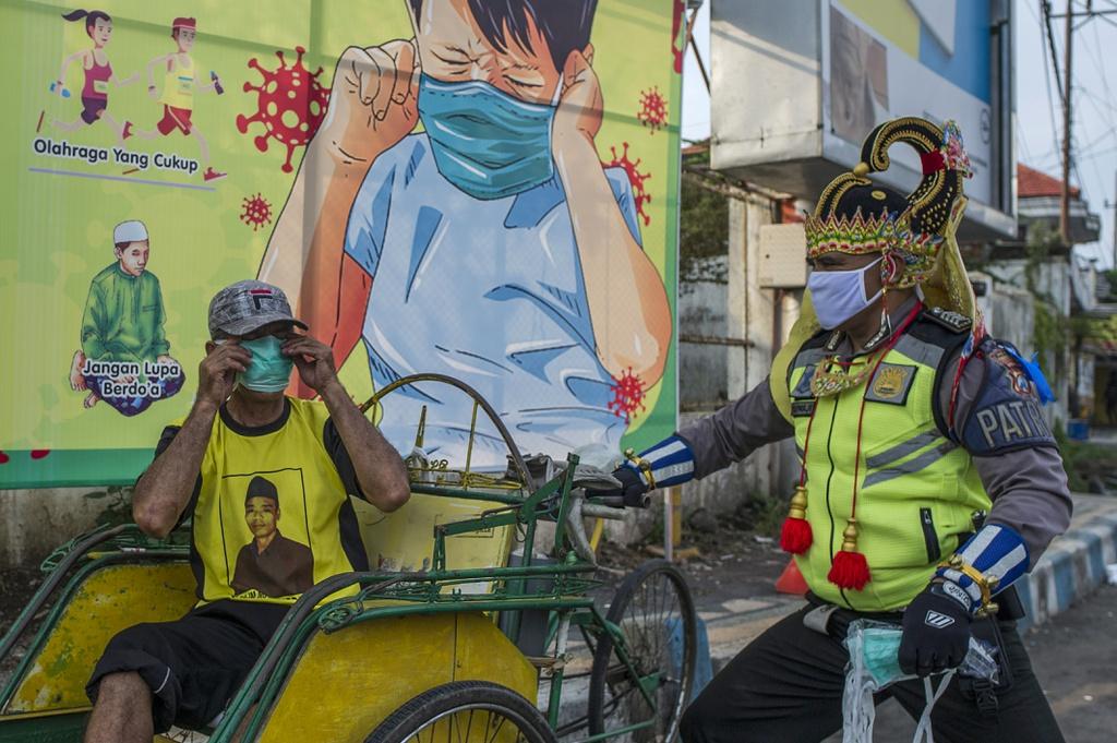Ở phía đông Java, Indonesia, một sĩ quan cảnh sát mặc trang phục siêu anh hùng đang phát khẩu trang cho người dân.