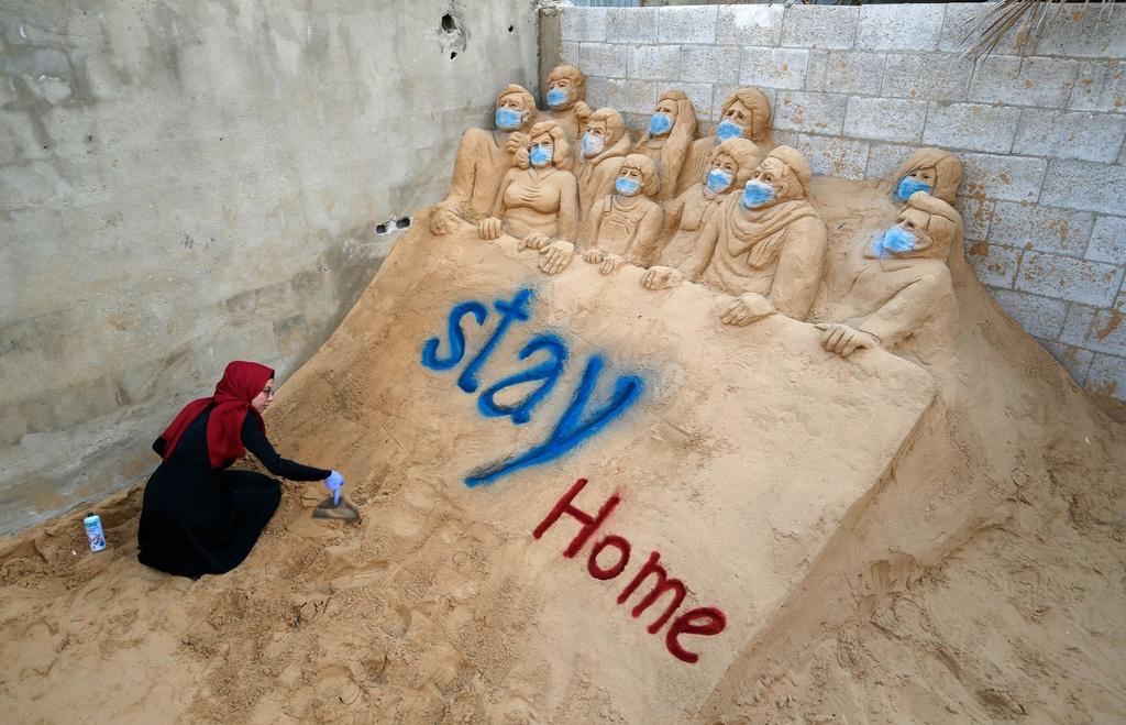 """Nghệ sĩ Rana al-Ramlawi đang tạo ra một tác phẩm điêu khắc cát ở thành phố Gaza, Palestine. Thông điệp """"Stay Home"""" nhằm kêu gọi mọi người """"Hãy ở yên tại nhà"""" trong mùa dịch."""
