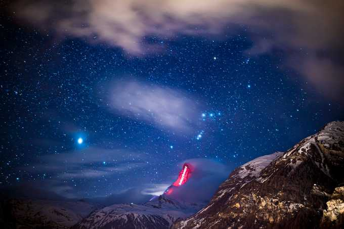 """Không phải là đỉnh núi cao nhất trong dãy Alps nhưng Matterhorn phủ tuyết là một trong những địa danh nổi tiếng, mang tính biểu tượng của đất nước. Ngọn núi hình kim tự tháp này có độ cao hơn 4.478 m so với mực nước biển; sườn núi dốc đứng. Do đó leo núi là thách thức không nhỏ cho những người yêu thể thao.  """"Hãy mạnh mẽ như ngọn núi Matterhorn, đứng vững cho đến khi cơn bão đi qua"""", đó cũng là dụng ý của chương trình. Ảnh: Valentin Flauraud/AP."""