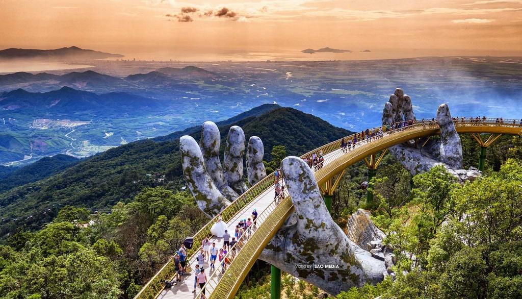 Cầu Vàng: Là một trong những điểm check-in hút khách nhất Đà Nẵng, thậm chí khiến cả cộng đồng du lịch thế giới xôn xao, Cầu Vàng xứng đáng nằm trong danh sách ghé thăm của bạn. Thiết kế ấn tượng với hai bàn tay khổng lồ nâng thân cầu uốn lượn như dải lụa, cùng khung cảnh tuyệt đẹp từ độ cao 1.400 m so với mực nước biển sẽ là background lý tưởng cho bạn lưu giữ kỷ niệm cùng người thân, bạn bè. Cây cầu này nằm trong quần thể du lịch Bà Nà Hills, rất thuận tiện cho du khách. Ảnh: Pullman-danang.