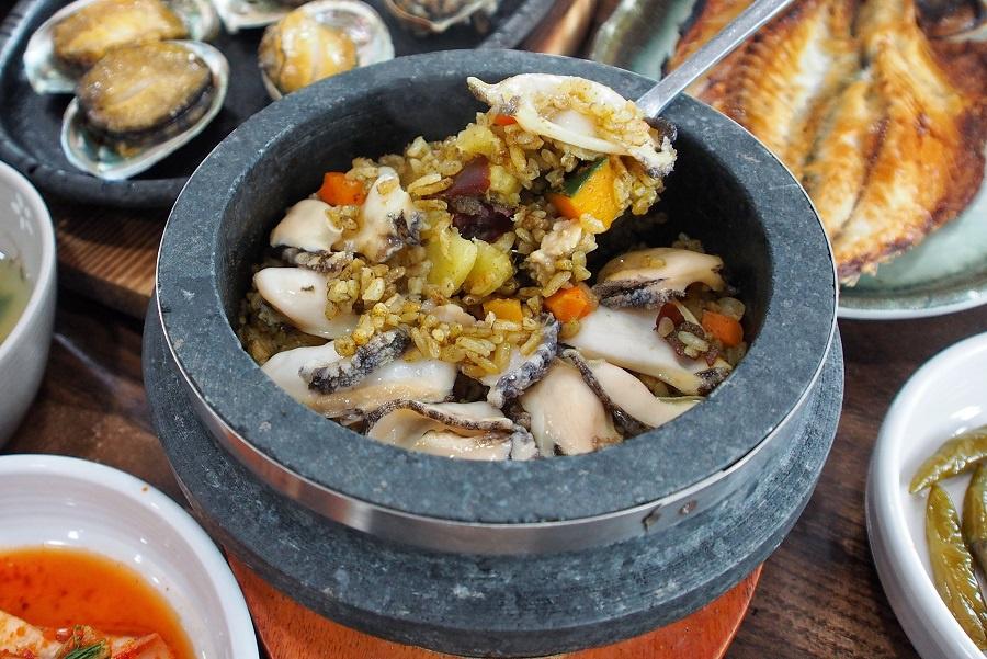 Ngoài ra, bạn còn có thể ăn thử món cơm rang bào ngư. Cơm được nấu cùng bí đỏ tạo ra màu vàng bắt mắt và bày trong thố đá nóng, với bào ngư cắt lát phía trên. Thực khách cần rưới một chút nước vào bát để hơi nước bốc lên khiến cơm mềm, béo ngậy và ngon hơn. Ảnh: Danielfooddiary.