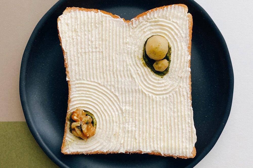 """Lát bánh mì lấy cảm hứng từ vườn đá - một nét văn hóa đặc trưng của Nhật Bản, làm từ kem chua, các loại hạt và matcha.   """"Tôi chọn chủ đề vào đêm hôm trước, nghĩ về những nguyên liệu mà tôi thích ăn vào sáng hôm sau. Sau đó, tôi đến cửa hàng tạp hóa, mua thêm các nguyên liệu mới và về nhà để sáng tạo. Khoảng 60% phần chuẩn bị cho món ăn được hoàn thành vào đêm hôm trước. Tôi thức dậy vào buổi sáng, hoàn thành tác phẩm sau đó chụp ảnh và ăn"""", nghệ sĩ cho biết. Ảnh: Manami Sasaki."""