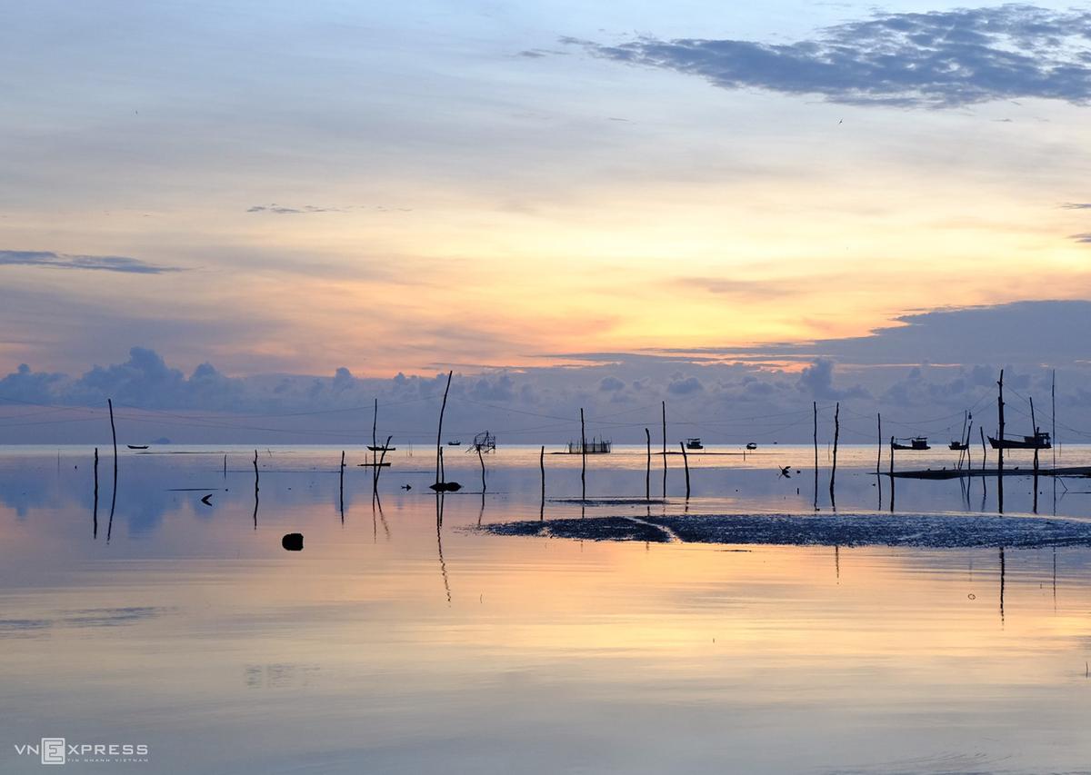 Thời điểm để ngắm bình minh ở Phú Quốc vào khoảng 5 - 6h sáng. Tuy nhiên, để canh đúng lúc mặt trời lên bạn nên tới sớm từ 4h30 để bắt được khoảnh khắc đẹp nhất. Đó là lúc vầng sáng lộ diện, khung cảnh biển Hàm Ninh hiện ra như mặt gương phẳng phản chiếu bầu trời ngày mới. Nếu có nhiều thời gian lưu lại làng chài, hãy dạo bộ quanh khu chợ cá, tìm mua sản vật địa phương hoặc đi thuyền ra những khu nhà bè để thưởng thức các món ngon từ hải sản.
