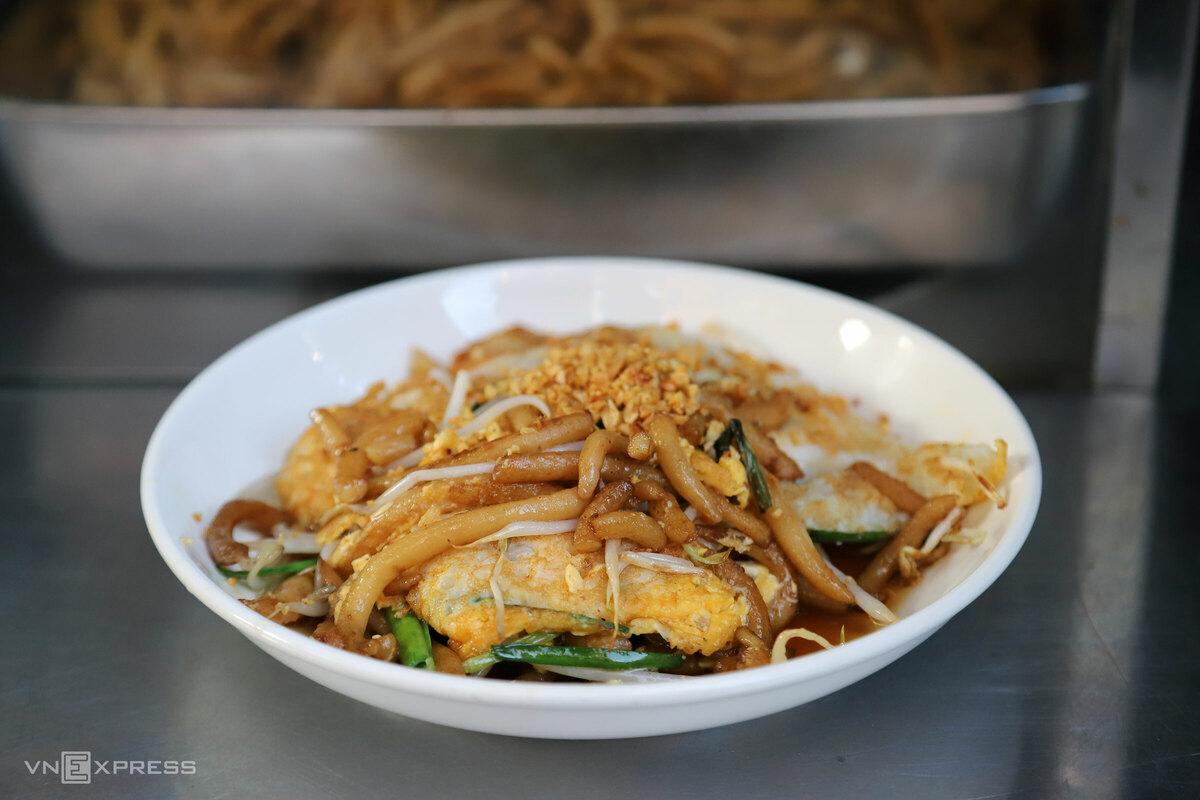 """Bánh lọt xào, hay lot-xa theo phiên âm tiếng Khmer, là món người Hoa du nhập vào Campuchia từ lâu, được kiều bào mang công thức về Việt Nam bán. Món ăn có thành phần đơn giản, gồm sợi bánh lọt làm từ bột gạo, giá, hẹ, trứng. Giá một đĩa từ 20.000 – 25.000 đồng.  Sợi bánh lọt tròn lẳn được xào sơ với màu dừa để có màu nâu và vị béo. Khi ăn, thực khách sẽ được hướng dẫn dùng các loại gia vị do chính chủ quán làm là giấm tỏi chua cay hoặc không cay. """"Hồi xưa xào bằng mỡ heo ngon lắm, giờ đổi thành dầu cho đỡ ngán và có thể dành cho người ăn chay"""", cô Cúc, chủ quán, cho biết."""