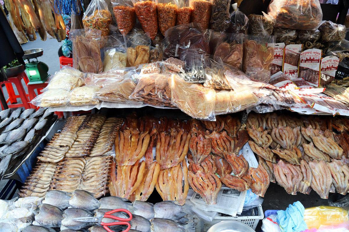 """Đồ khô được bán ở chợ gồm lạp xưởng, thịt trâu bò gác bếp, nhái, rắn và nhiều loại cá được đánh bắt từ Biển Hồ (Campuchia) như cá lóc, cá tra, cá sặt, cá sủ, cá chốt, cá trèn, nhái, rắn bông súng… Các loại khô có giá khoảng 200.000 – 500.000 đồng/ kg, có thể mua lẻ từng khúc cá.  """"Khô Cam khác khô miền Tây"""", một số người ghé mua quầy Tư Xê nhận xét. Khách mua đồ khô chủ yếu là dân địa phương, gồm người Việt, người gốc Campuchia, người gốc Hoa…"""