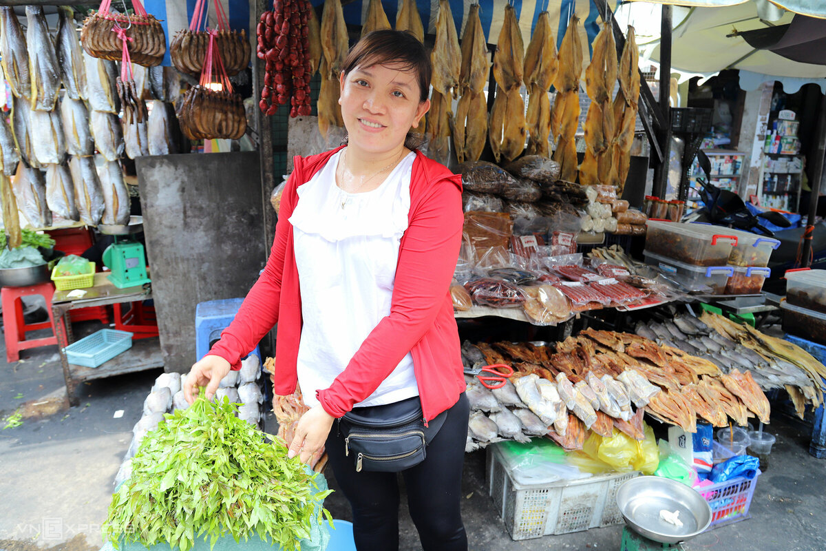 """Ngay sau lưng nhà Tư Xê, hàng khô Hai Nhỏ do chị Trần Thị Dung (35 tuổi) đứng bán được 10 năm, đã có mặt từ năm 1970 của mẹ chị làm chủ, vẫn giữ hình thức sạp gỗ chứ không thuê hay xây quầy.   """"Hai mẹ con đều biết chế biến đồ khô, nhưng vẫn phải nhập từ Campuchia về vì ở đây không có chỗ phơi nắng, và cá mới bắt bên đó phải xử lý luôn mới ngon"""", chị Dung chia sẻ."""