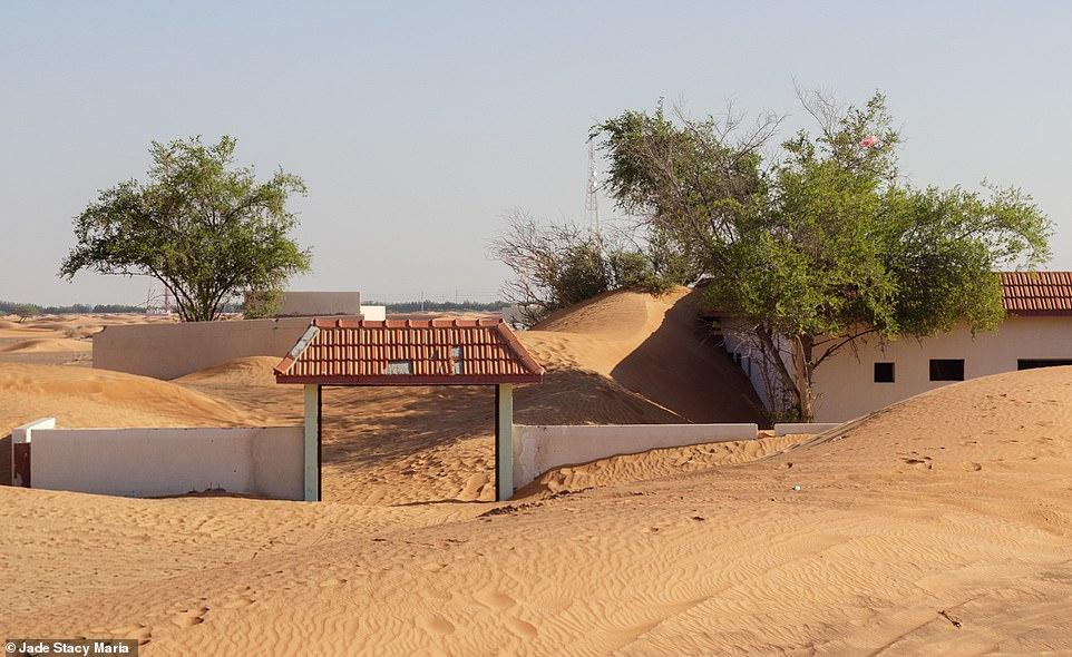 Dubai thường được biết đến với hình ảnh những tòa nhà chọc trời và vô số dịch vụ xa xỉ chỉ dành cho giới lắm tiền. Tuy nhiên, nhiếp ảnh gia Jade Stacy Maria lại có hứng thú tìm về những góc khuất đầy ma mị của thành phố nhà giàu này. Cách trung tâm Dubai khoảng 61 km, du khách có thể ghé thăm Al Madam - một ngôi làng bỏ hoang đang bị cát xâm chiếm.