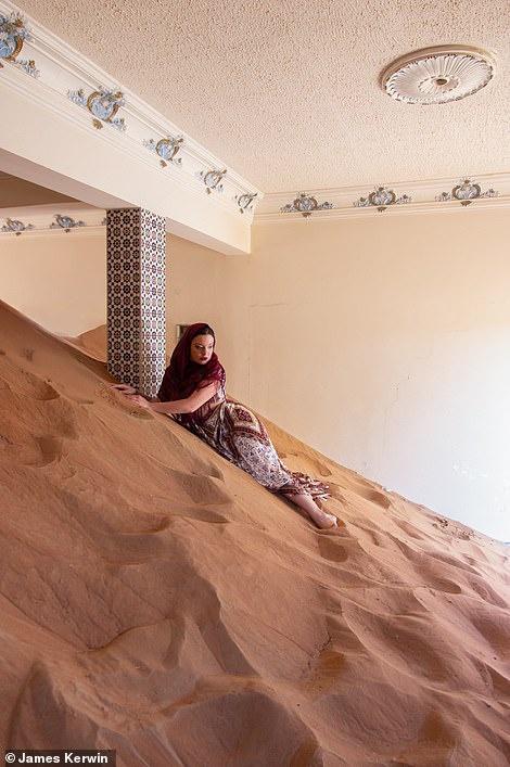 Một số ngôi nhà bị cát lấp cao tới gần chạm nóc. Trong ảnh, nhiếp ảnh gia Jade đang nằm trên cát chụp hình.