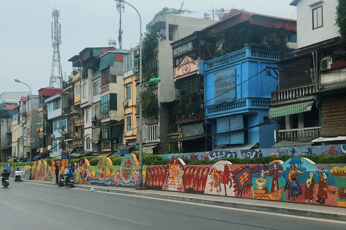 """Trải dài gần 4 km dọc theo đê Sông Hồng, con đường gốm sứ hiện giữ kỷ lục Guinness """"Bức tranh gốm dài nhất thế giới"""". Những bức tranh đầy màu sắc nổi bật trên con đường tấp nập, sử dụng gốm sứ được sản xuất tại Bát Tràng.  Tranh mô tả các thời kỳ khác nhau trong lịch sử Việt Nam. Các nghệ sĩ đã bắt đầu thực hiện dự án này vào năm 2007 và đã hoàn thành vào năm 2010 để chào đón đại lễ 1.000 năm Thăng Long. Ảnh: Diggers2004/Wikimedia Commons."""