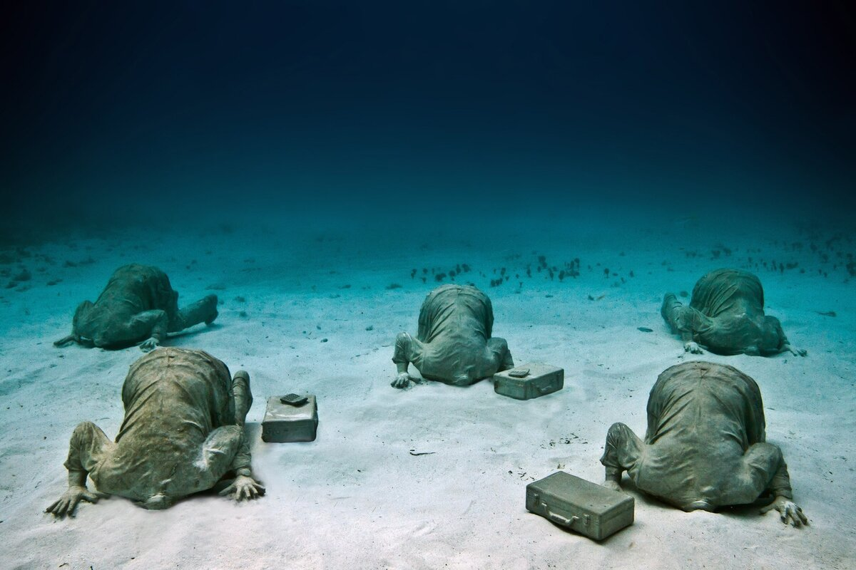 """Bộ sưu tập Nhân viên ngân hàng ở độ sâu 6m, bao gồm nhiều bức tượng nam giới trong bộ đồ công sở vùi đầu trong cát. Đây là một trong những tác phẩm mang tính châm biếm, được Taylor tạo ra sau khi tham dự hội nghị về biến đổi khí hậu ở Cancun. """"Ai cũng thừa nhận vấn đề to lớn đang diễn ra với hệ sinh thái đáy biển, nhưng khi được hỏi về hành động, không ai muốn 'thò đầu' ra để làm gì đó"""", ông chia sẻ. Ảnh: Jason deCaires Taylor."""