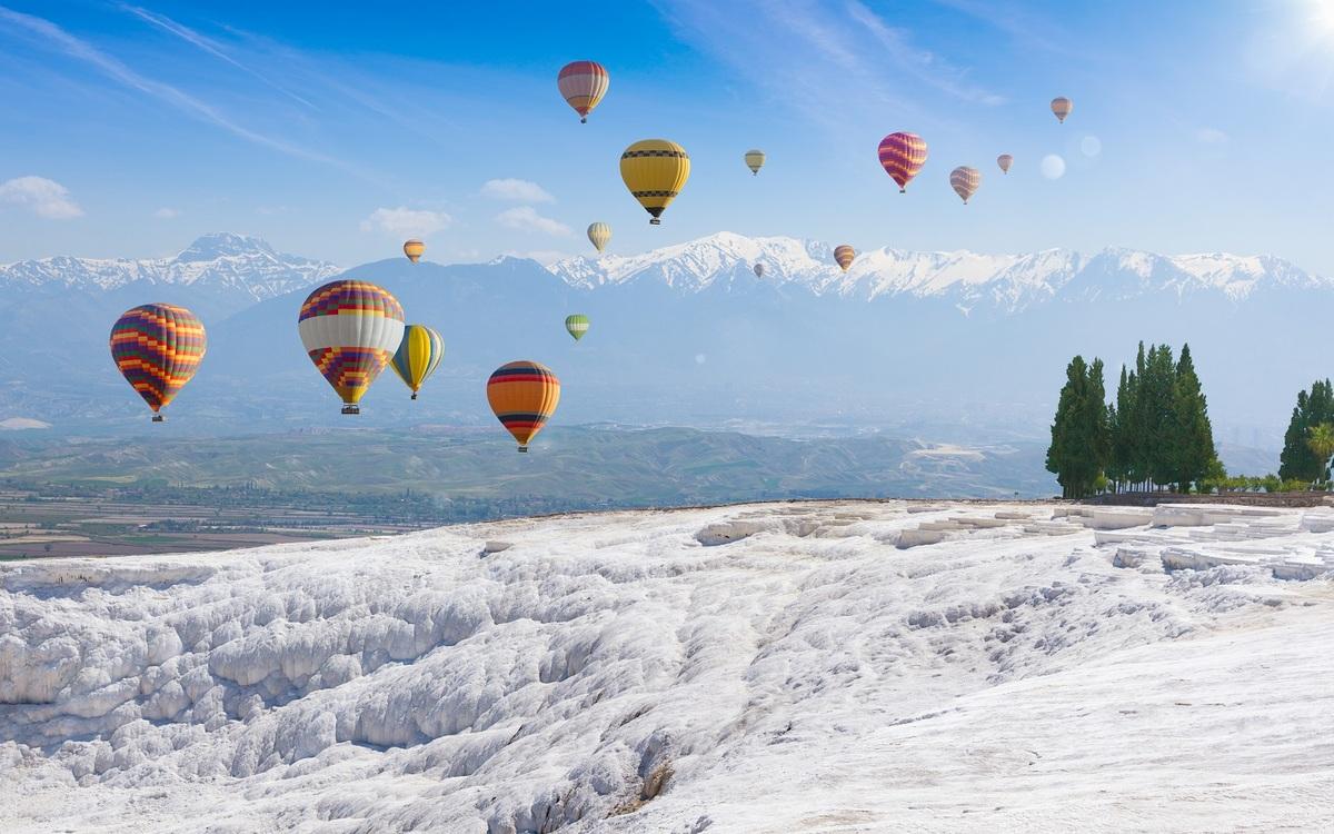 Tới đây, du khách có thể trải nghiệm ngồi khinh khí cầu hay chơi dù lượn để ngắm nhìn những hồ nước lấp lánh và thành phố cổ Hierapolis từ trên cao. Giá tour tham quan bằng khinh khí cầu trong 2 tiếng có giá khoảng 130 EUR ( hơn 3 triệu đồng). Ảnh: IgorZh/Shutterstock.