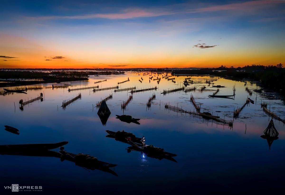 Le lói trong bức tranh rạng đông là ánh sáng từ đèn pin đội đầu của ngư dân, đang chiếu rọi trên sọt cá tép vừa đánh bắt.   Bức ảnh được chụp trên đầm Quảng Lợi, huyện Quảng Điền, nằm trong bộ ảnh Nhịp sống bình minh Ngư Mỹ Thạnh của nhiếp ảnh gia Kelvin Long (sống và làm việc tại Huế) thực hiện.