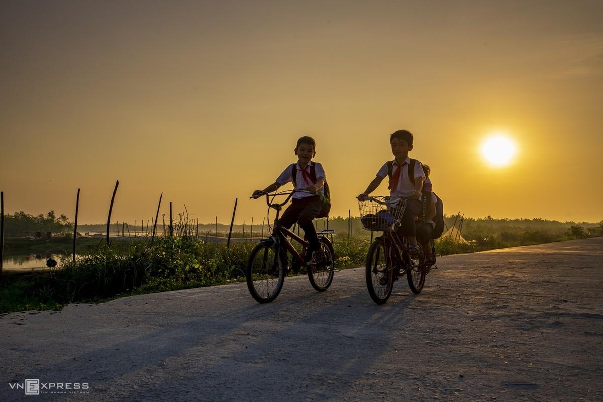 Trẻ em đạp xe đi học lúc bình minh trên đường bê tông cạnh đầm Quảng Lợi mang đến bức tranh quê hương thanh bình.