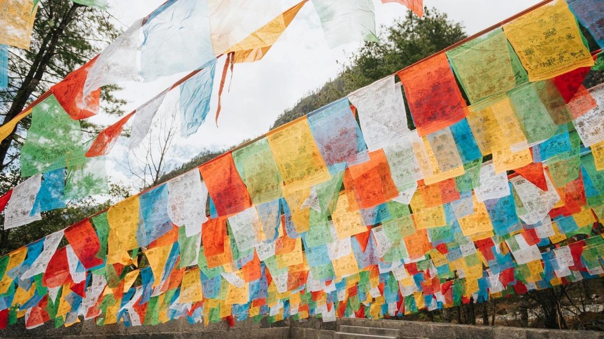 """Bạn sẽ thấy người dân treo Lungta, những lá cờ cầu nguyện Tây Tạng với nhiều màu sắc khác nhau ở mọi nơi.  Lungta trong tiếng Tây Tạng có nghĩa là """"ngựa gió"""". Người Tây Tạng tin rằng, biểu tượng của ngựa gió tiêu biểu cho sự chuyển hóa của cái ác thành cái thiện, những điều không may thành cát tường, thịnh vượng; chướng ngại trở thành cơ hội may mắn. Cờ được làm bằng vải hình vuông hoặc hình chữ nhật màu trắng, xanh dương, vàng, xanh lá và đỏ.  Trên mặt lá cờ được trang trí bởi các hình ảnh và những lời cầu nguyện. Nằm ở chính giữa vị trí trung tâm cờ là ngựa gió, đại diện cho Tam Bảo của Phật giáo. Ở bốn góc của lá cờ là những linh thú: Garuda (một loài chim thần) tượng trưng cho trí tuệ, rồng tượng trưng cho quyền năng, hổ tượng trưng cho lòng tin và sư tử tuyết đại diện dũng cảm."""
