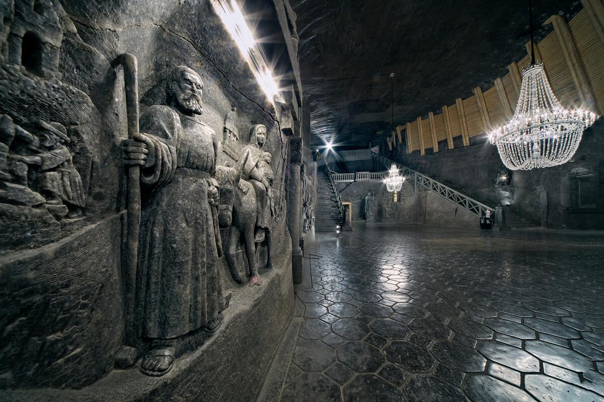Nằm ở độ sâu hơn 100 m là nhà nguyện St Kinga trang trí rất nhiều đèn chùm và tượng, tranh phù điêu trên những bức tường đá muối. Kinga là một trong những vị thánh quan trọng nhất ở Ba Lan và Lithuania, thánh bảo trợ của những thợ mỏ.  Sau khi bước xuống dãy cầu thang lớn, du khách sẽ đặt chân tới sảnh lớn xung quanh là các bức phù điêu, và cuối phòng là ban thờ thánh Kinga. Ảnh: wieliczka-saltmine.