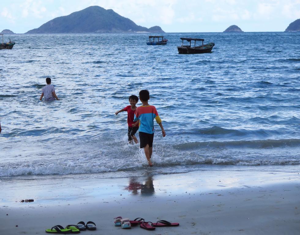 Bạn nhỏ nô đùa trên bãi biển chiều với nụ cười hồn nhiên, trong trẻo